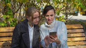 Two attractive woman watching photos on the smartphone stock video footage