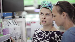 Two attractive womans choosing body care products In supermarket. stock video footage