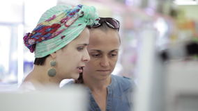 Two attractive womans choosing body care products In supermarket. stock footage