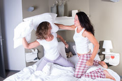 Two attractive women in bed having a pillow fight.  Royalty Free Stock Images