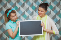 Two attractive women with blank chalkboard in hands. Girls hold blackboard. Studio shot. Blue background, copy space Stock Photo