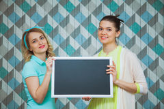 Two attractive women with blank chalkboard in hands. Girls hold blackboard. Studio shot. Blue background, copy space Royalty Free Stock Photos