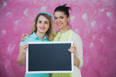 Two attractive women with blank chalkboard in hands. Girls hold blackboard. Studio shot. Pink background, copy space Royalty Free Stock Images