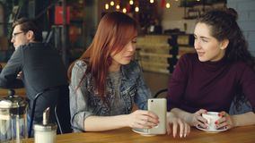 Two attractive women in casual clothes are having girl time in cafe talking and holding coffee cup and smartphone. Nice. Cafe interior, customers and modern stock video