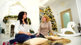 Two attractive women chatting and laughing in festive mood and sitting on floor against fireplace and Christmas tree in stock video footage