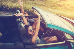 Two attractive women in a convertible car Stock Photos