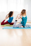 Two attractive women doing asana one legged king pigeon Royalty Free Stock Photo