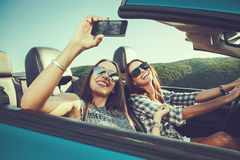 Two attractive women dtaking selfe in a convertible car Stock Image