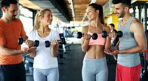 Two attractive women exercising with personal trainers. In gym stock image