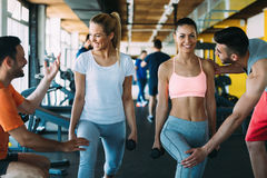Two attractive women exercising with personal trainers. In gym royalty free stock photography