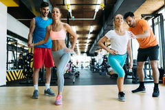 Two attractive women exercising with personal trainers. In gym Stock Photography