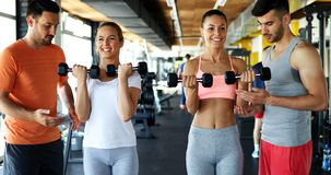 Two attractive women exercising with personal trainers Royalty Free Stock Images