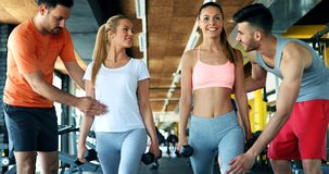 Two attractive women exercising with personal trainers. In gym Royalty Free Stock Image