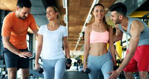 Two attractive women exercising with personal trainers Stock Images