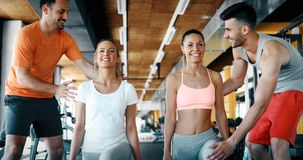 Two attractive women exercising with personal trainers. In gym Royalty Free Stock Photo