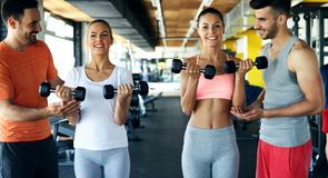 Two attractive women exercising with personal trainers. In gym stock images