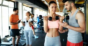 Two attractive women exercising with personal trainers. In gym Royalty Free Stock Images