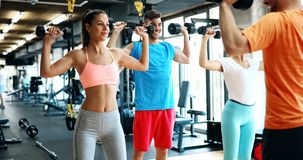 Two attractive women exercising with personal trainers. In gym Royalty Free Stock Photos