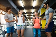 Two attractive women exercising with personal trainers. In gym stock photo