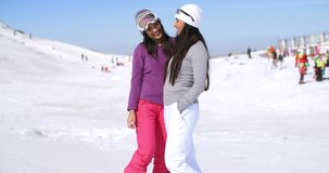Two attractive women friends at a ski resort stock footage