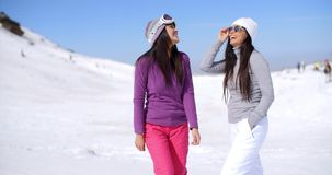 Two attractive women friends at a ski resort stock video