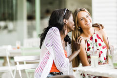 Two attractive women gossiping and whispering outdoors in a cafe. In summer stock image