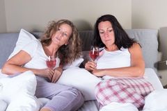 Two attractive women having a drink in bed Royalty Free Stock Photos
