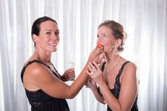 Two attractive women - one is feeding the other with strawberry.  Stock Images