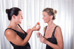 Two attractive women - one is offering strawberry to her friend Royalty Free Stock Image