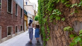 Two attractive women in panamas walking on the alley along the green wall stock photography