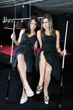 Two attractive women playing snooker. Two attractive women in black dresses playing snooker Royalty Free Stock Photos