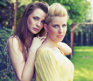 Two attractive women posing in the garden Royalty Free Stock Photos