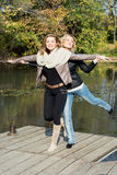 Two attractive women posing by the pond in the autumn park Royalty Free Stock Images
