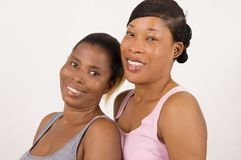 Two young women smiling with beautiful skin isolated on light background royalty free stock photos