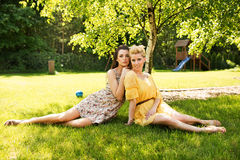 Two attractive women resting on the flower meadow Stock Photography