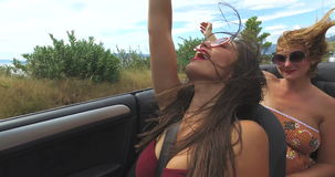 Two attractive women riding in cabriolet along dalmatian coast stock video footage