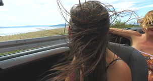 Two attractive women riding in cabriolet along dalmatian coast stock footage