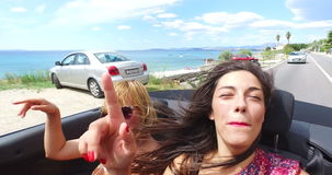 Two attractive women riding in the windy back seat of convertible. Two beautiful women at the back of convertible enjoying the ride with wind in their hair stock video footage