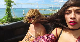 Two attractive women riding in the windy back seat of convertible. Two beautiful women at the back of convertible enjoying the ride with wind in their hair stock footage