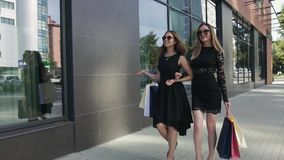 Two attractive women with shopping bags enjoying their walk down the street. Slow motion stock footage
