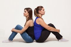 Two attractive women sit back to back royalty free stock photography