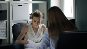 Two attractive women sit at table and look through documents in office. Various kinds of sheets of paper lie in front of them on desk. Some graphs and stock video footage