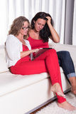 Two attractive women sitiing on the couch and looking on tablet Stock Image