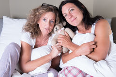Two attractive women sitting in bed and dreaming Royalty Free Stock Photos