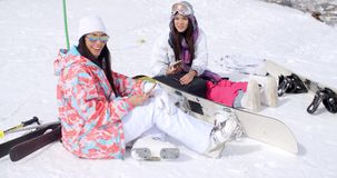 Two attractive women snowboarders relaxing stock footage