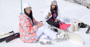 Two attractive women snowboarders relaxing Stock Photos