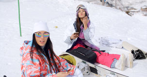 Two attractive women snowboarders relaxing Royalty Free Stock Photography