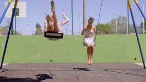 Two attractive women swinging in a park. Two attractive women swinging on swings in a park in trendy summer dresses enjoying the warm sunshine stock video footage