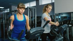 Two attractive women are trained in the gym on the elliptical trainer.  stock footage