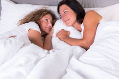 Two attractive women waking up next to each other in bed Stock Photo